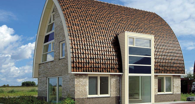A single-family house covered with shaded copper brown Flandern tiles